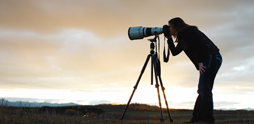 Holly Nicoll peers into her camera mounted on a tripod with a telephoto lens attached. Prairie sunset is the backdrop.