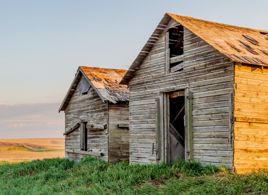 A couple of old wooden grain bins sit on the side of a gravel road