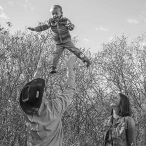 A cowboy throws his son high in the air while his wife looks on, smiling.