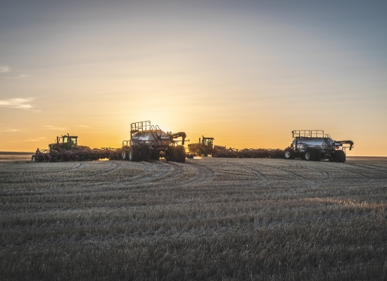 Farm seeding equipment waits in the field as the sun sets.