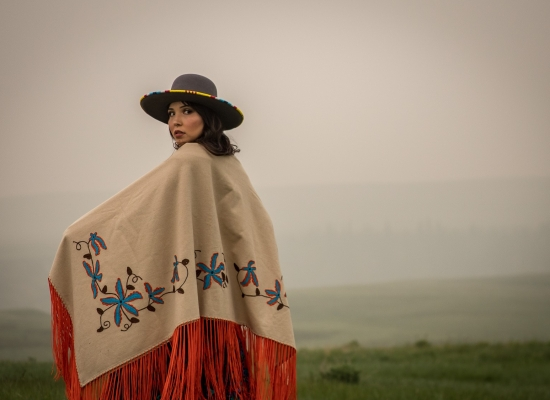 A Blackfoot women looks backwards in a portrait with smoky skies in the background